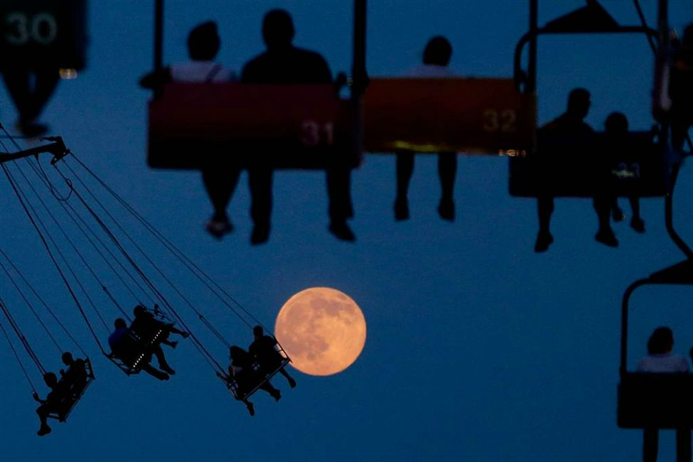 The moon rises as people sit on rides at the State Fair Meadowlands, on July 1, in East Rutherford, N.J.